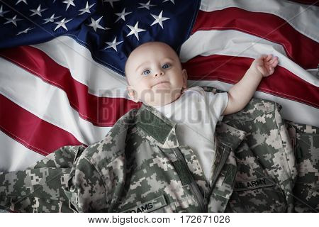 Cute little baby in military uniform on flag