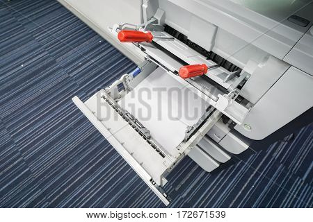 red screwdriver on the printer tray for repair assistance