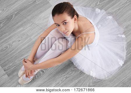 Little ballerina sitting on floor, top view