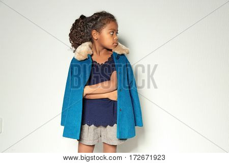 Cute little African American girl in coat against light wall. Fashion concept