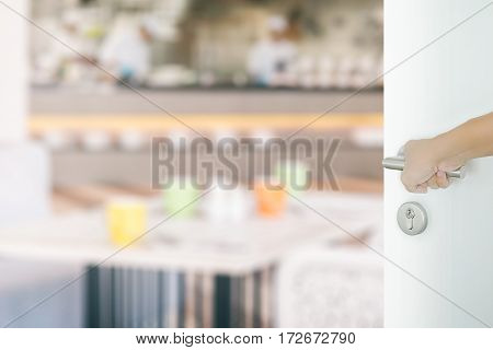 Man Hand Opening White Door To Restaurant Interior With Colorful Tables Set For Meal
