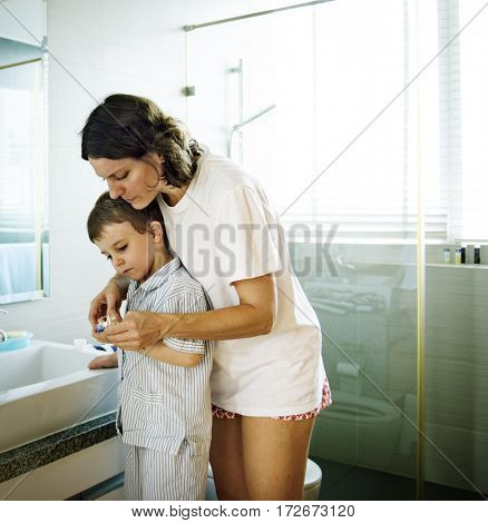 Mom Teaching Son Use Toothbrush in the Toilet