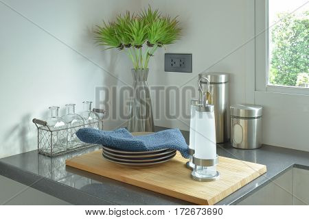 Dishes And Bottles On Black Counter Top In The Kitchen