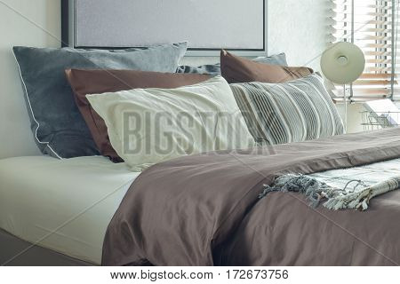 Modern Classic Style Deep Brown, Gray And White Bedding And Reading Lamp In The Bedroom