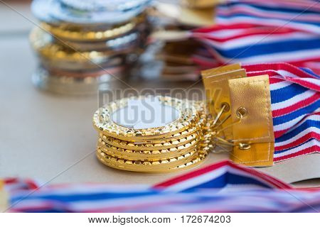 stacks of gold silver and bronze medals selective focus on the closest stack with blurred background