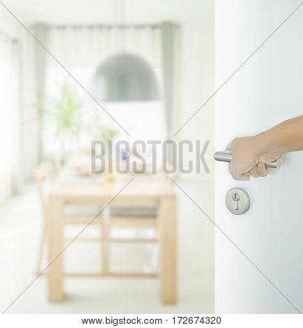 Man Hand Opening White Door To Dining Table And Comfortable Chairs In Modern Home