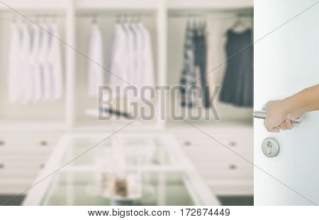 Man Hand Opening White Door To Closet Room With White Shirt And Hat On A Table