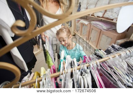 Child with mother in a children's store. Happy girl choosing clothes. Family are shopping