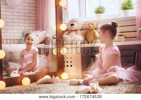 Cute little girl dreams of becoming a ballerina. Child in a pink tutu dancing in a kids room.