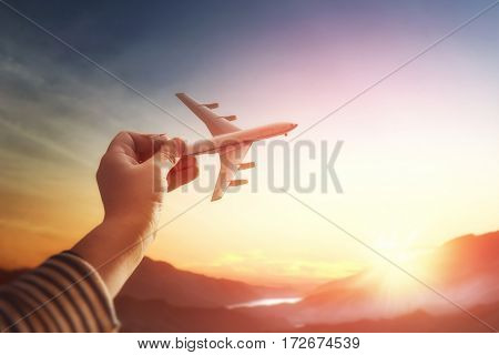 Child plays with a toy airplane in the sunset and dreams of journey. Hand with small plane close up.