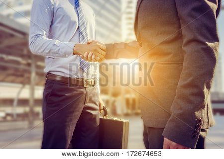 Success and Happiness concept Business man handshake at city outside office.