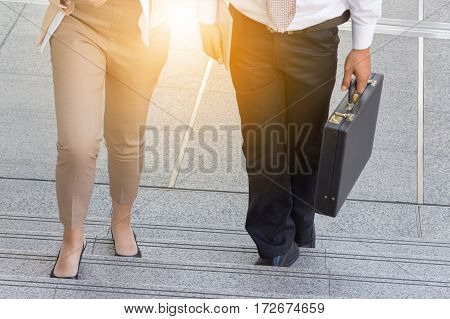 Businessman and Business woman walking up stairs with bags to office.