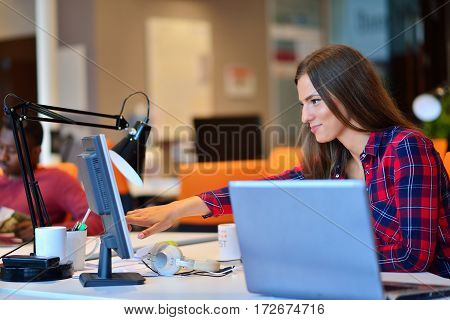 Happy businesswoman working on her laptop in the office.