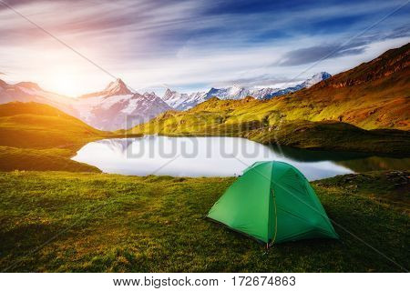 Alpine valley glowing by sunlight. Popular tourist attraction. Dramatic and picturesque scene. Location place Bachalpsee in Swiss alps, Grindelwald, Bernese Oberland, Europe. Beauty world.