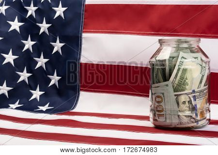 glass jar with dollars standing on a US flag