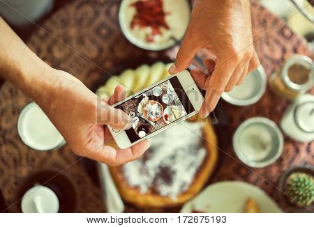 man using smartphone in cafe. smartphone white screen. hand holding smartphone. Hands with the phone close-up pictures of food. Pancake cereal and coffee for breakfast. vintage tone.