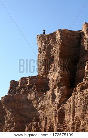 man with arms raised to the top of the mountain canyon