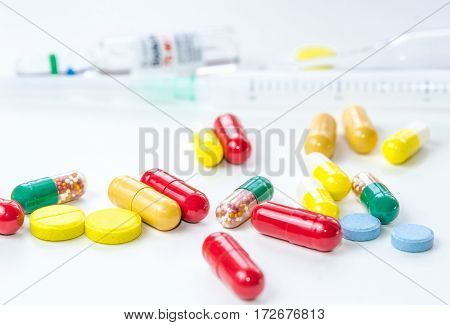Colorful medicine pills, drugs and capsules with syringe and ampule on a white background. Selective focus. Close-up macro shot.