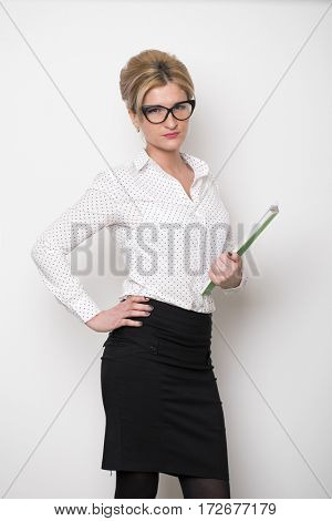 Secretary in the office. Portrait of a beautiful young blonde woman in a white blouse and black skirt on white wall background