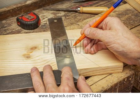 Woodworker Draws A Line On A Wooden Board