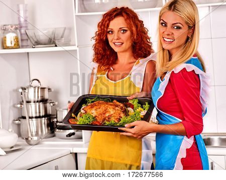 Women in kitchen is cooking roast meat food in oven. Chicken is oven- tray with lettuce leaf. Two housewife wearing apron in white home interior preparing barbecue dinner for girl friends.