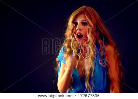 Frightened woman screaming with fear indoor at halloween night. Horror. Girl with tousled hair bawl presses to her hands on black background.