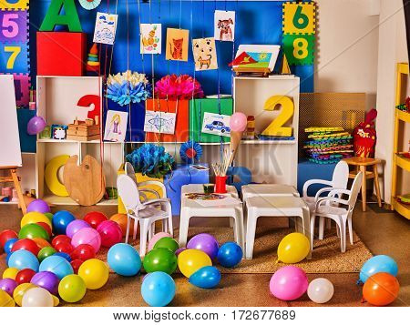 Kindergarten interior decoration child picture on wall. Preschool class waiting kids. Colour balloons on floor. Playroom with white table. Art room education children's creativity. Mess in classroom.