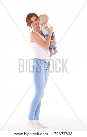 Young happy mother with sweet child stands on a white background. Happy family. Six month.