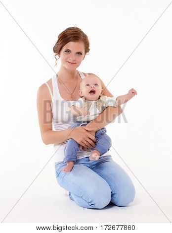 Young happy mother with sweet child sit on a white background. Happy family. Six month.