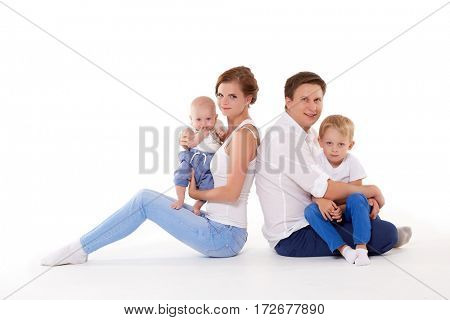 Young parents with sweet  children sit on a white background. Happy family. Six month and four years.