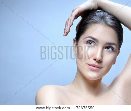 Beauty Spa Woman with Perfect skin Portrait. Beautiful Brunette Spa Girl . Young Caucasian with Fresh looking Skin. Beauty Woman Face Closeup. Blue background. Looking up. Studio shot