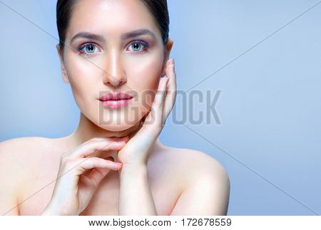beauty closeup portrait of attractive young caucasian woman brunette on blue background studio shot lips face skin care hands near the face looking at camera spa. Touching her perfect skin. copy spacy