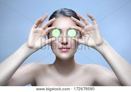 beauty closeup portrait  attractive young caucasian woman brunette on blue background studio shot lips face care eyes head and shoulders cucumbers in hands vegetable healthy eating eyes cucumber mask