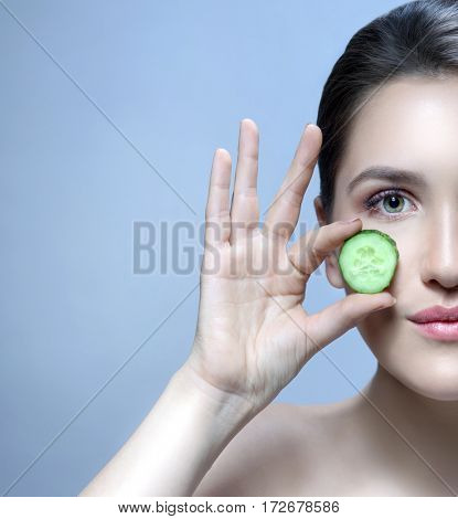 beauty closeup portrait of attractive young caucasian woman brunette  on blue background studio shot lips face care eyes head and shoulders looking at camera hands cucumbers vegetable healthy eating