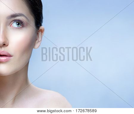 beauty closeup portrait of attractive young  caucasian woman brunette on blue background studio shot lipscare face skin care  looking up