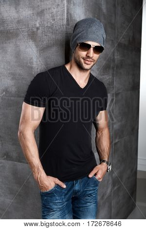 Portrait of trendy athletic young man in cap and sunglasses.