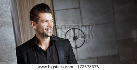 Portrait of happy young caucasian businessman in black suit.