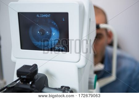 Man looking at eye test machine in ophthalmology clinic