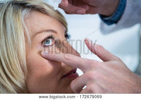 Optometrist putting drops into patients eyes in ophthalmology clinic