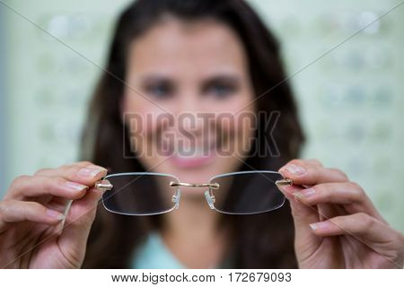 Female customer holding spectacles in optical store Smiling female customer holding spectacles in optical store