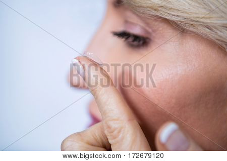 Woman applying contact lens in ophthalmology clinic