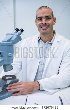 Portrait of smiling male optometrist with microscope in ophthalmology clinic