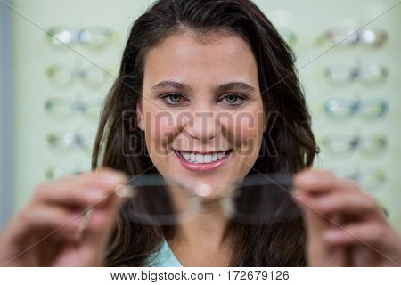 Smiling female customer holding spectacles in optical store