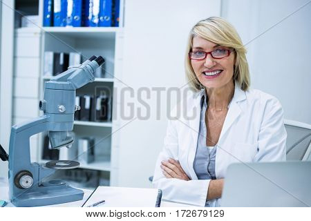 Portrait of smiling optometrist sitting with arms crossed in ophthalmology clinic