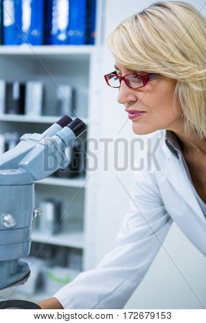 Female optometrist looking through microscope in ophthalmology clinic