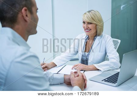 Female optometrist talking to male patient in ophthalmology clinic