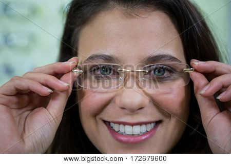 Portrait of smiling female customer wearing spectacles in optical store