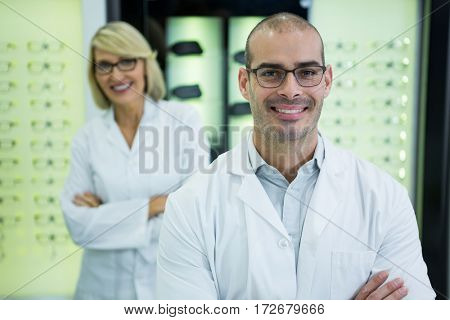 Portrait of smiling optometrists standing with arms crossed in optical store