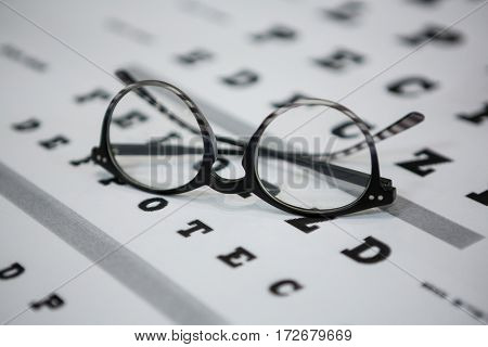 Close-up of spectacles on eye chart in ophthalmology clinic