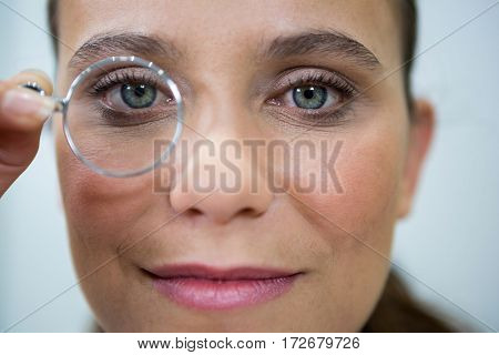 Female optometrist looking through magnifying glass in ophthalmology clinic